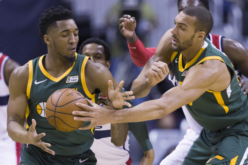 Utah Jazz guard Donovan Mitchell, left, gets the ball from center Rudy Gobert (27), from France, with Washington Wizards forward Trevor Ariza, back le...