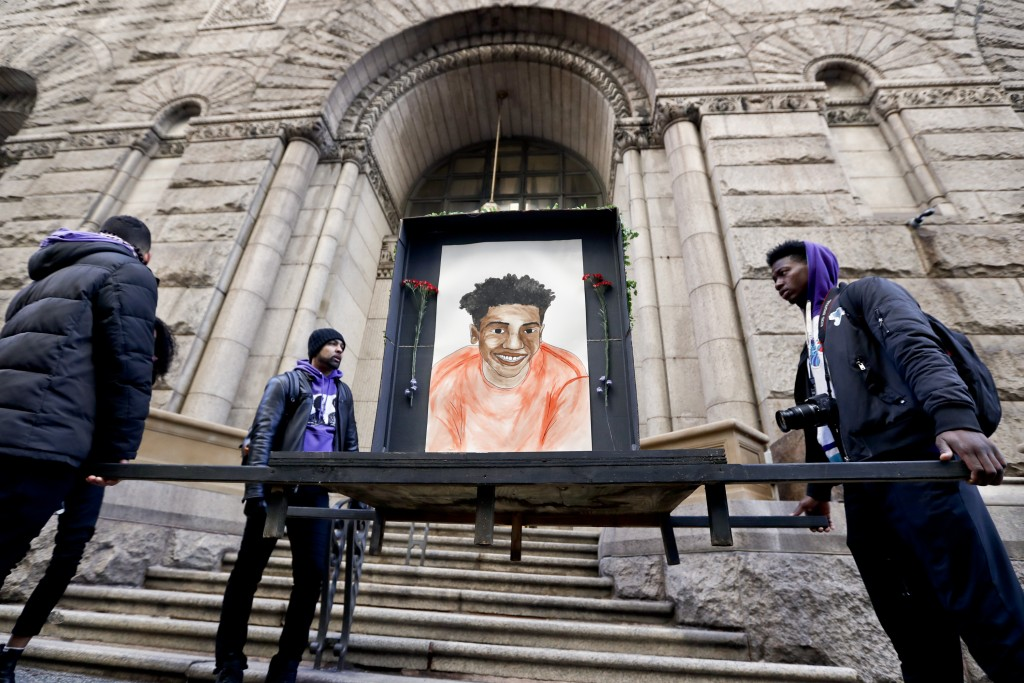 Farooq Al-Said, left, Jasiri X, center, and Jarrion Manning, right, hold a memorial display with a drawing of Antwon Rose II in front of the court hou...