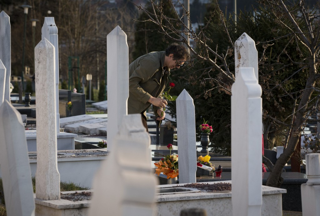 In this Sunday, March 17, 2019 photo, a man places flowers at the section of a cemetery for 1990s war victims in Sarajevo, Bosnia-Herzegovina. Nearly ...