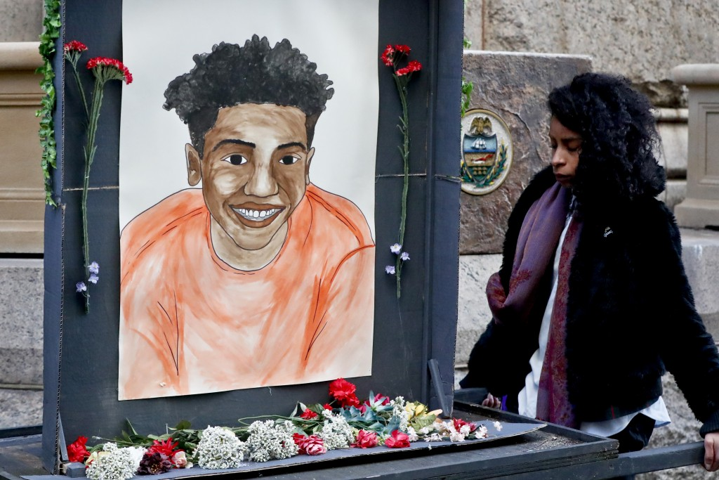 A woman who did not want to be identified holds a memorial display with a drawing of Antwon Rose II in front of the court house on the first day of th...