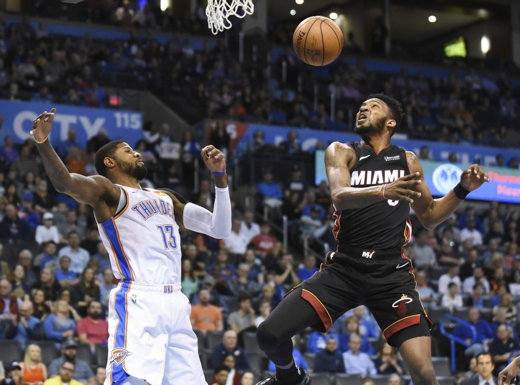 Oklahoma City Thunder forward Paul George, left, tries to get to a rebound before Miami Heat forward Derrick Jones Jr. in the first half of an NBA bas...