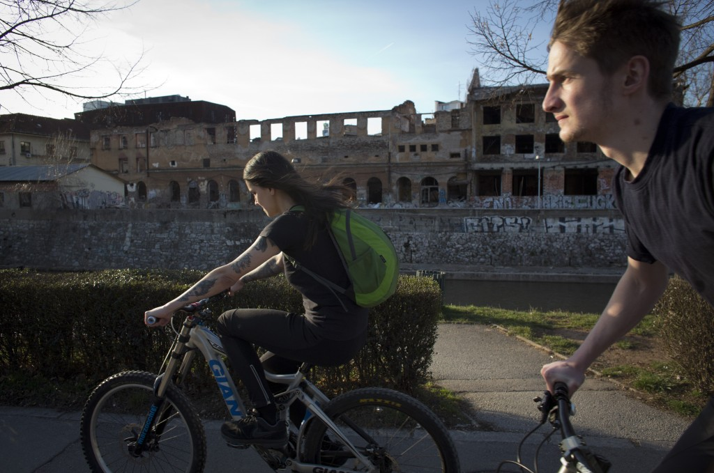 In this Sunday, March 17, 2019 photo, cyclists ride past war damaged buildings in Sarajevo, Bosnia-Herzegovina. Nearly a quarter of a century since Bo