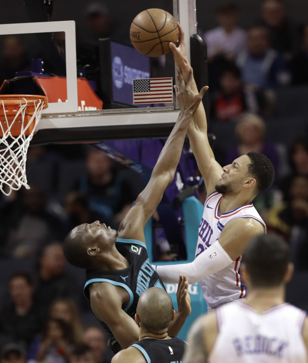 Philadelphia 76ers' Ben Simmons (25) is fouled by Charlotte Hornets' Bismack Biyombo (8) during the first half of an NBA basketball game in Charlotte,
