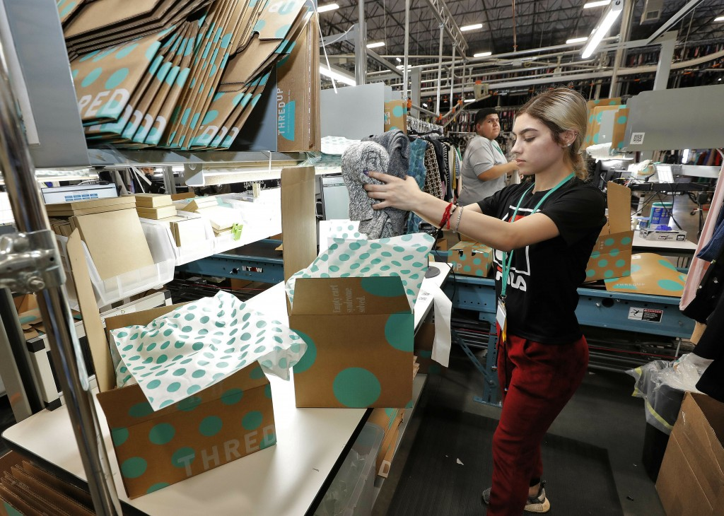 In this Tuesday, March 12, 2019, photo Yakaranday Arce packs sold clothing for shipment at the ThredUp sorting facility in Phoenix. Charitable organiz