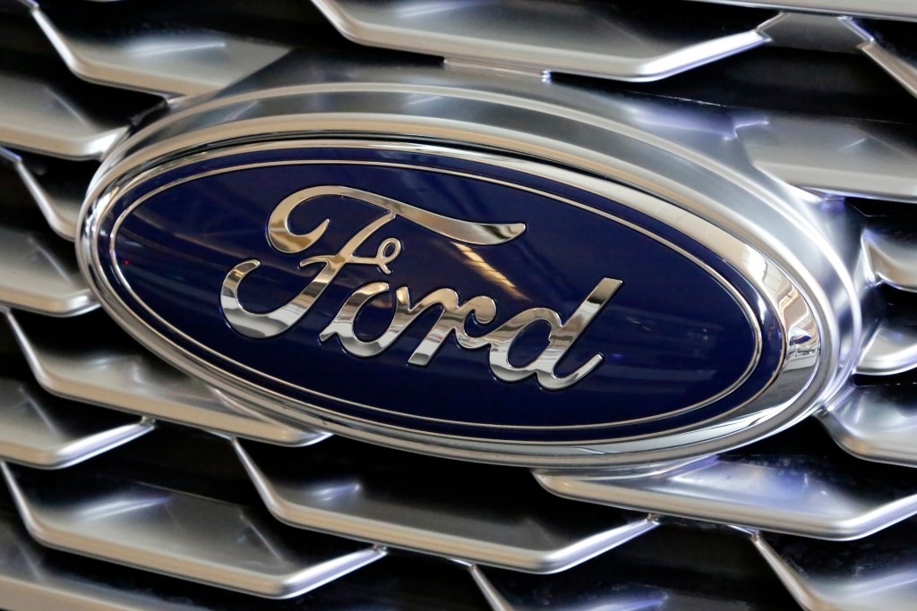 FILE- This Feb. 15, 2018, file photo shows a Ford logo on the grill of a car on display at the Pittsburgh Auto Show. Ford Motor Co. is repackaging a p...