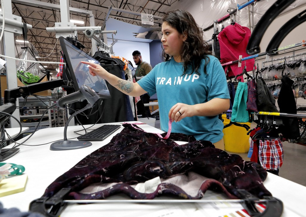 In this Tuesday, March 12, 2019, photo Jasmine Valladares enters measurements as she itemizes clothing at the ThredUp sorting facility in Phoenix. Cha