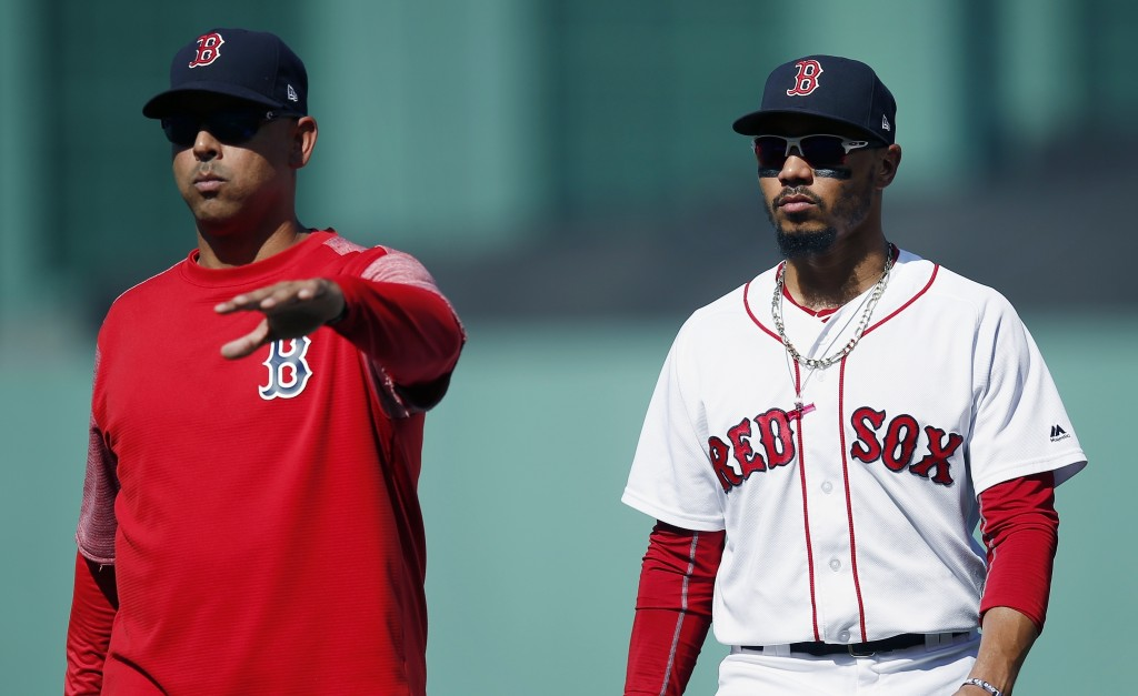FILE - In this Sept. 16, 2018, file photo, Boston Red Sox manager Alex Cora, left, escorts Mookie Betts off the field during the sixth inning of the t