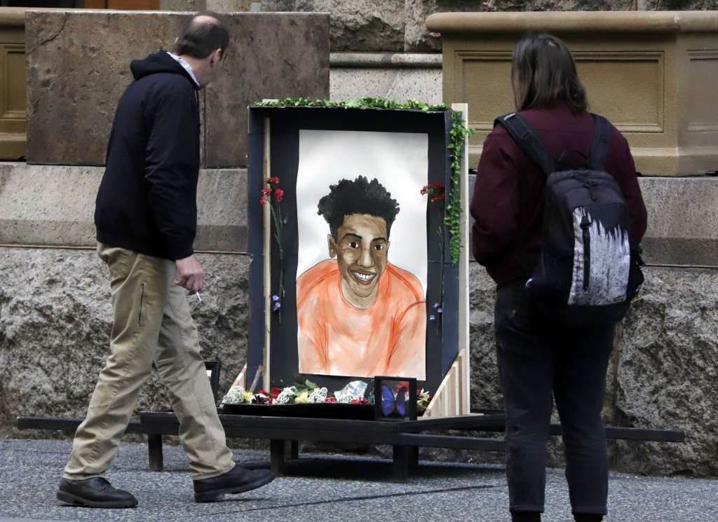Passers-by looks at a memorial display with a drawing of Antwon Rose II in front of the Allegheny County courthouse on the second day of the trial for...