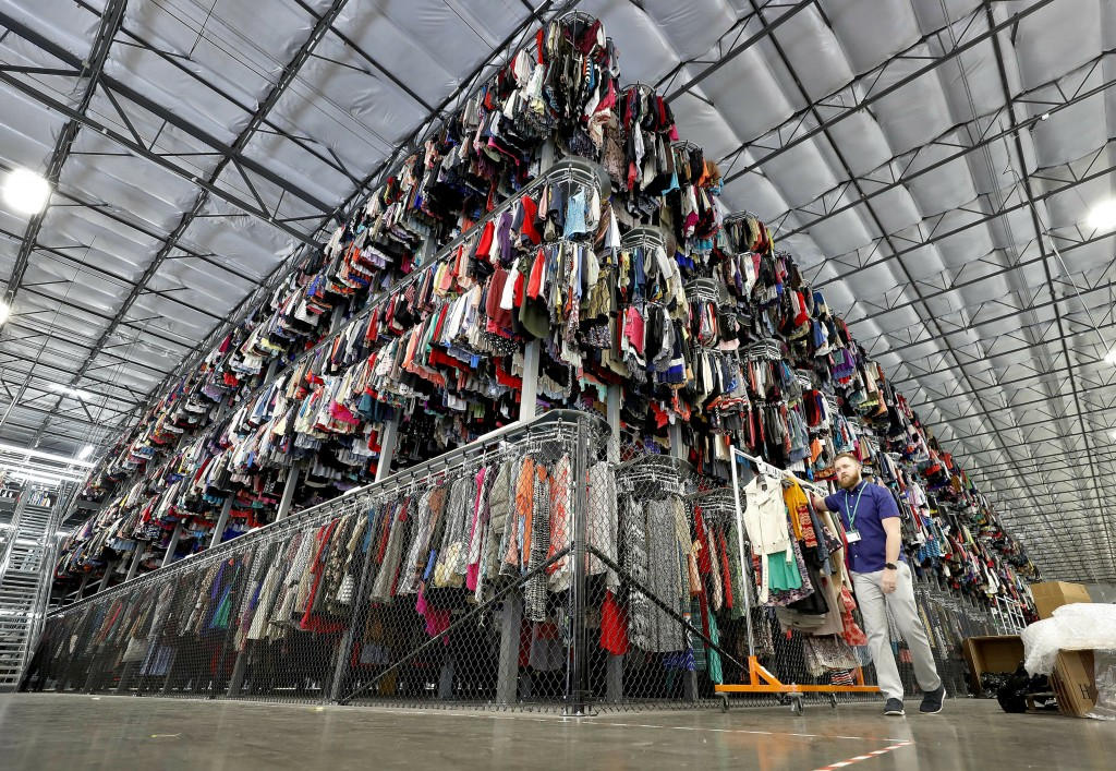 In this Tuesday, March 12, 2019, photo thousands of garments are stored on a three-tiered conveyor system at the ThredUp sorting facility in Phoenix.