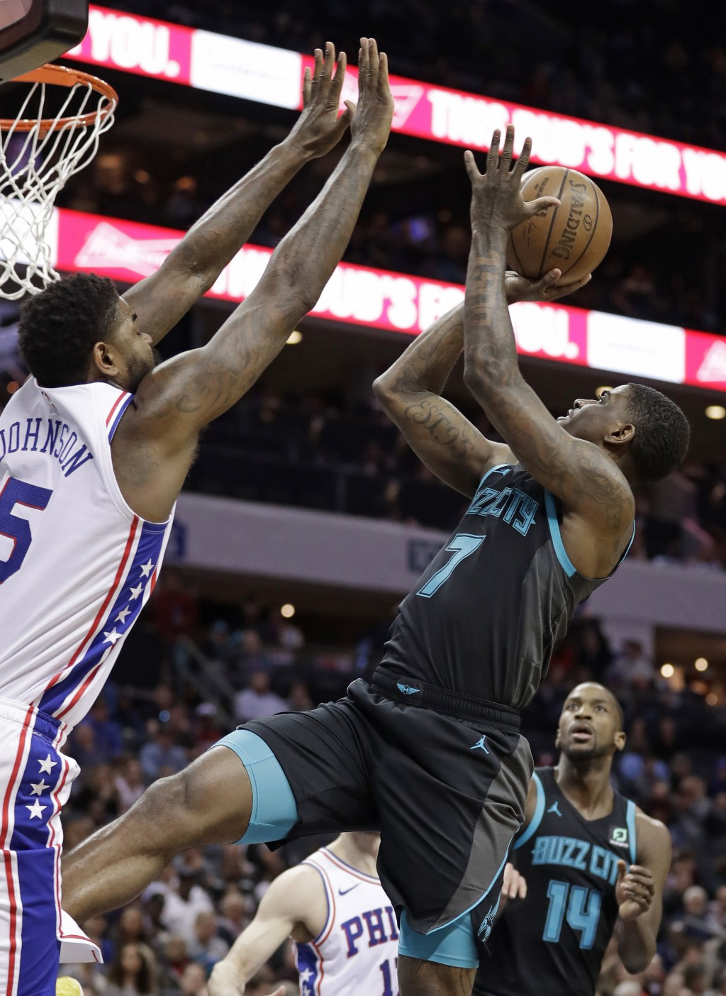 Charlotte Hornets' Dwayne Bacon (7) shoots against Philadelphia 76ers' Amir Johnson (5) during the first half of an NBA basketball game in Charlotte,