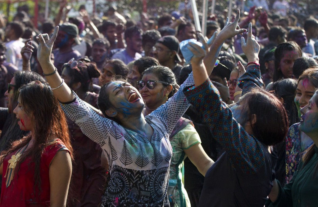 In this Wednesday, March 20, 2019, file photo, revelers dance as they celebrate Holi, also known as the Festival of Colors, organized by the Hindu com...