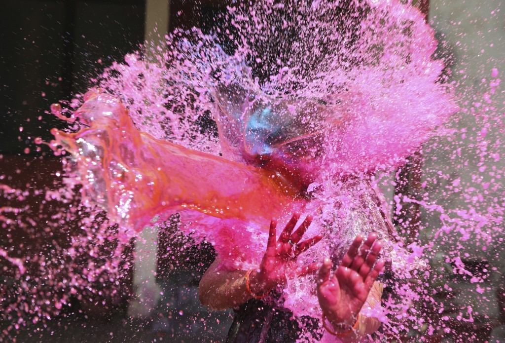 In this Thursday, March 21, 2019, file photo, a girl gestures with her hands as colored water is splashed on her during celebrations marking Holi fest...