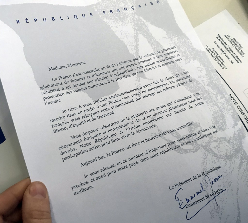 A document signed by French President Emmanuel Macron and given to Britain's Catherine Norris Trent holds is pictured during a naturalization ceremony