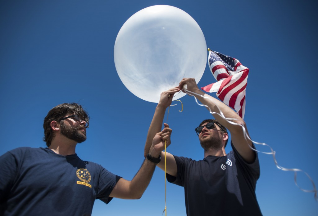 In this March 13, 2019 photo, Project OWL team leader Bryan Knouse ties a U.S. flag to a helium-filled balloon carrying a tiny transmitter, aided by D