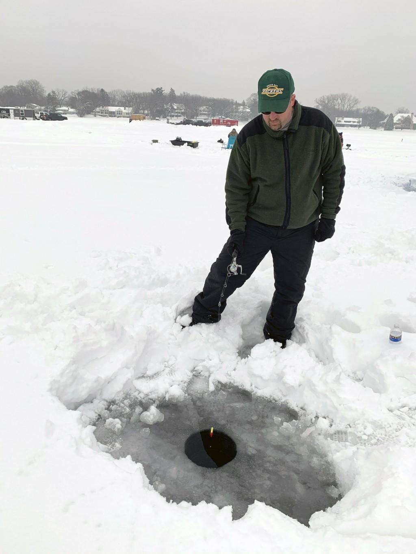 In this Feb. 23, 2019 photo, Paul Riemer of Eden Prairie, Minn., fishes through a hole in the ice of Lake Minnetonka in Wayzata, Minn. Since 1970, Min