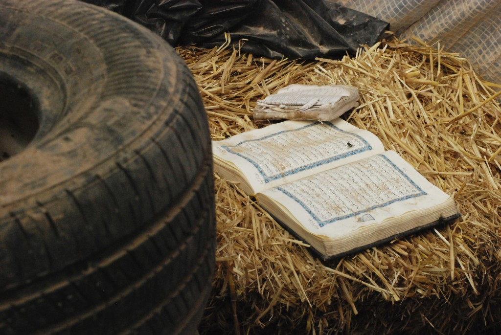 FILE - In this Aug. 10, 2018 file photo, copies of the Quran are left behind at a makeshift living compound in Amalia, N.M. Five former residents of t