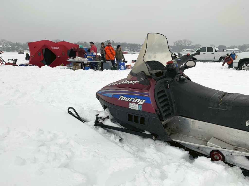 In this Feb. 23, 2019 photo, a snowmobile sits on the snow-covered ice of Lake Minnetonka in Wayzata, Minn., while ice anglers gather in the backgroun