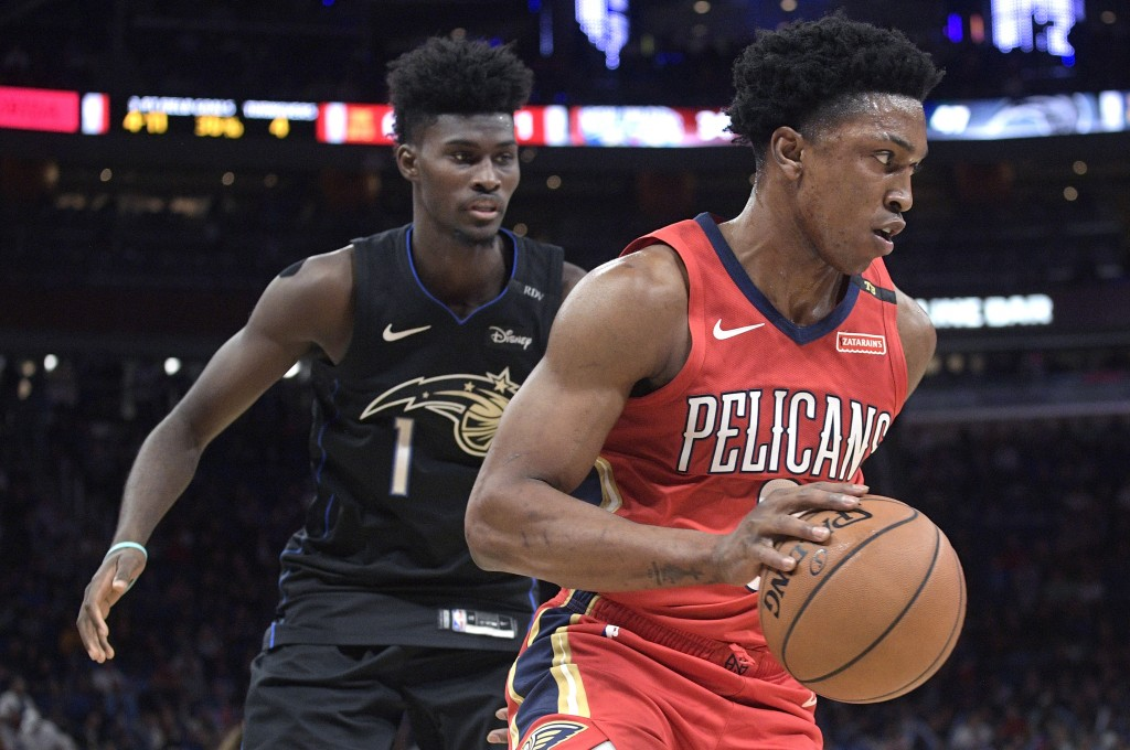New Orleans Pelicans forward Stanley Johnson, right, drives past Orlando Magic forward Jonathan Isaac during the first half of an NBA basketball game ...