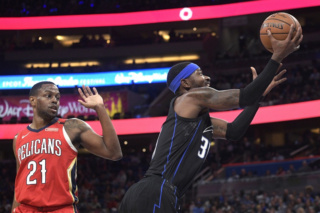 Orlando Magic guard Terrence Ross (31) shoots next to New Orleans Pelicans forward Darius Miller (21) during the first half of an NBA basketball game ...