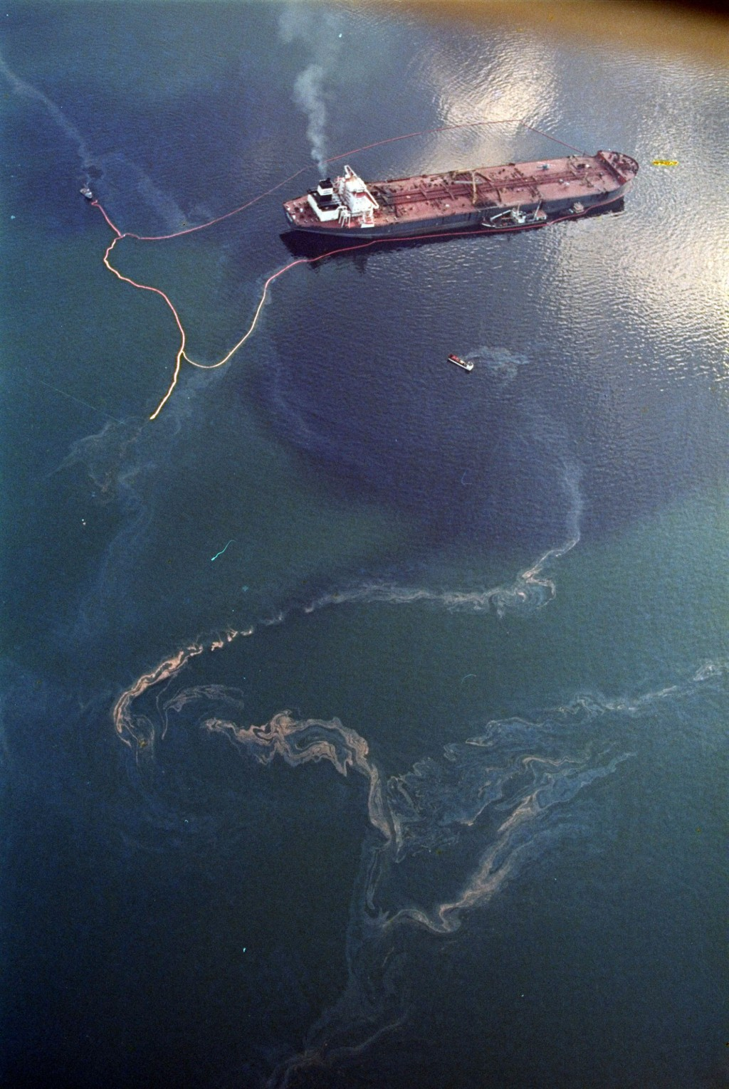 FILE - In this April 9, 1989, file photo, crude oil from the tanker Exxon Valdez, top, swirls on the surface of Alaska's Prince William Sound near Nak