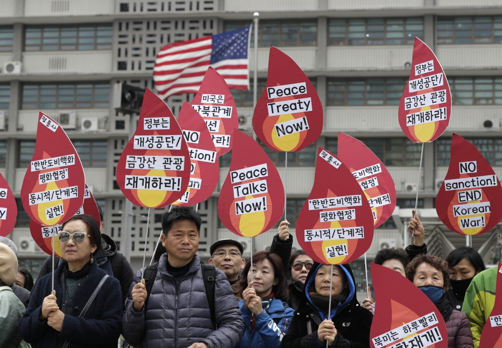Protesters hold signs during a rally demanding the denuclearization of the Korean Peninsula and peace treaty near the U.S. embassy in Seoul, South Kor...