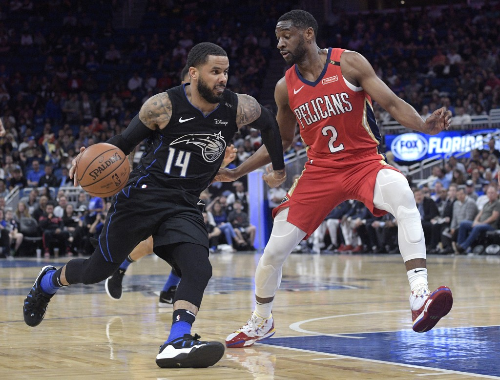 Orlando Magic guard D.J. Augustin (14) drives to the basket in front of New Orleans Pelicans guard Ian Clark (2) during the first half of an NBA baske...