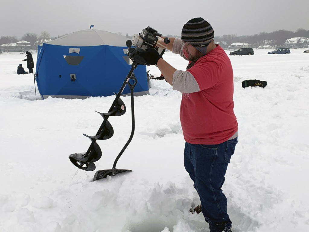 In this Feb. 23, 2019 photo, Jason Kong uses an auger to drill holes in Lake Minnetonka in Wayzata, Minn., as he prepares to go ice fishing. Since 197