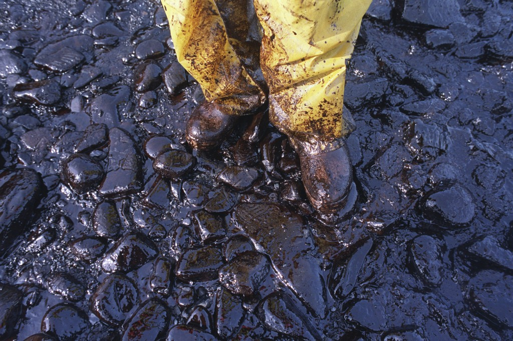 FILE - In this April 11, 1989, file photo, thick crude oil that washed up on the cobble beach of Evans Island sticks to the boots and pants of a local...