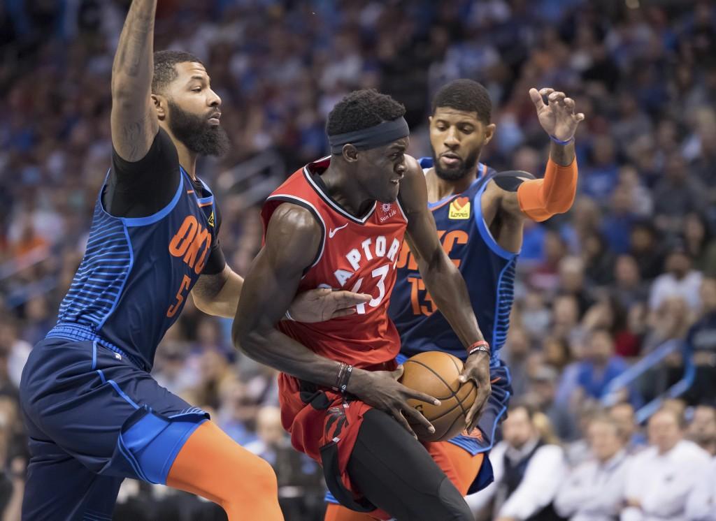 Toronto Raptors forward Pascal Siakam (43) drives to the basket between Oklahoma City Thunder forward Markieff Morris, left, and forward Paul George d...