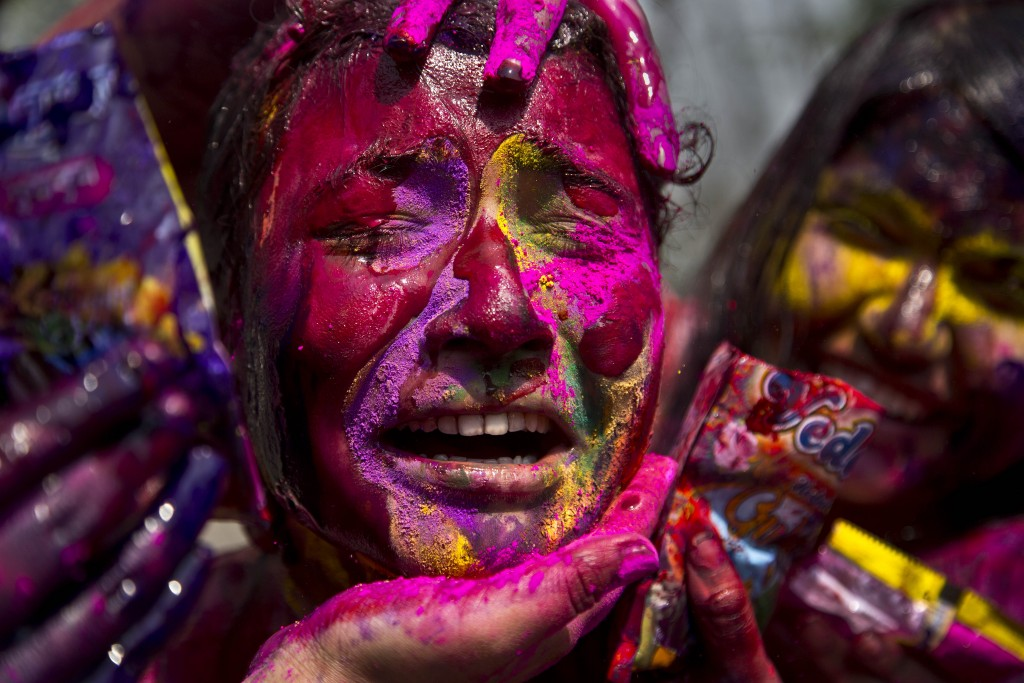 In this Thursday, March 21, 2019, file photo, an Indian girl grimaces as her face is smeared with colored powder during celebrations marking Holi, the...