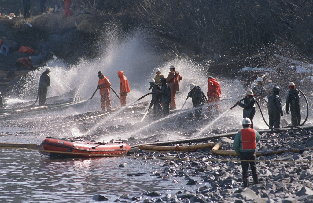 FILE - In this April 21, 1989, file photo, crews use high pressured hoses to blast the rocks on this beachfront on Naked Island, Alaska. Just after mi...