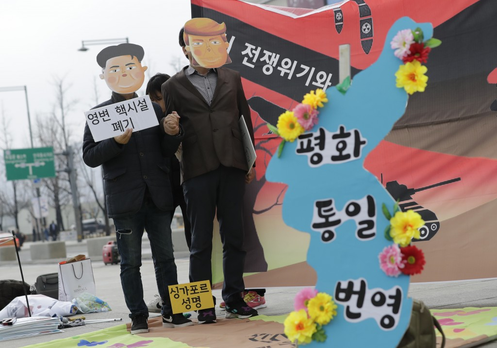 Protesters wearing masks of U.S. President Donald Trump and North Korean leader Kim Jong Un stand near the map of Korean Peninsula during a rally dema...