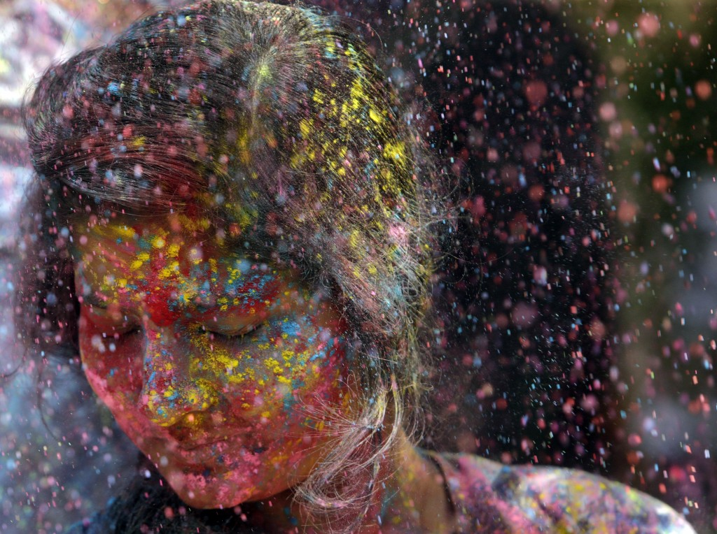 In this Thursday, March 21, 2019, file photo, revelers throw colored powder on a woman during celebrations marking Holi, the Hindu festival of colors,...