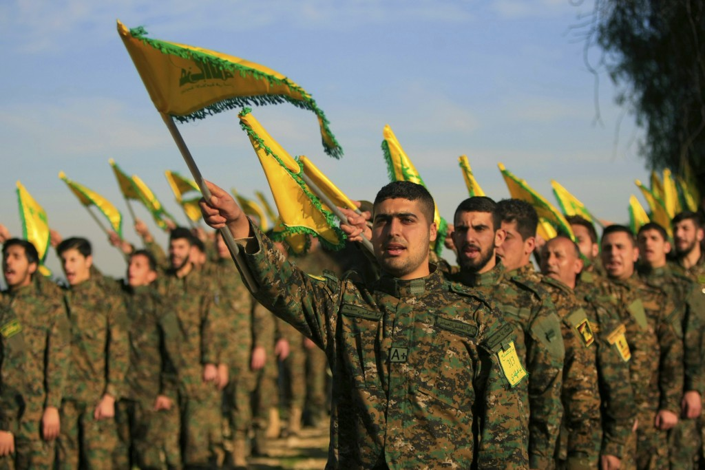FILE - In this Feb. 13, 2016 file photo, Hezbollah fighters hold flags as they attend the memorial of their slain leader Sheik Abbas al-Mousawi, who w