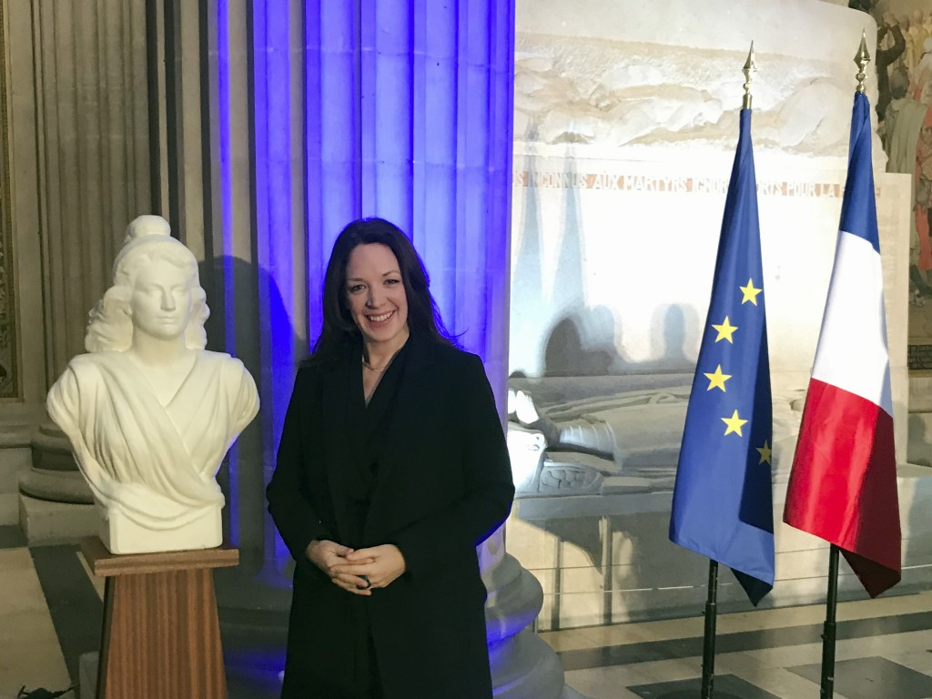 Britain's Catherine Norris Trent poses next to a bust of Marianne, left, symbol of the French Republic, and the French, right, and European flags afte