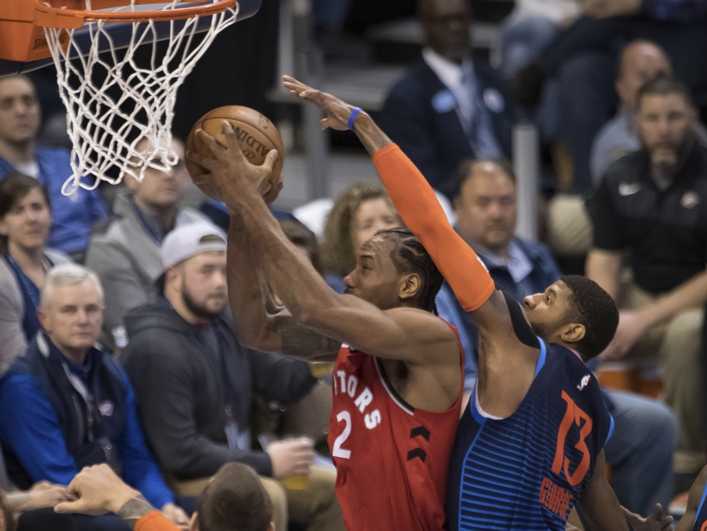 Toronto Raptors forward Kawhi Leonard (2) shoots while defended by Oklahoma City Thunder forward Paul George (13) during the first half of an NBA bask...