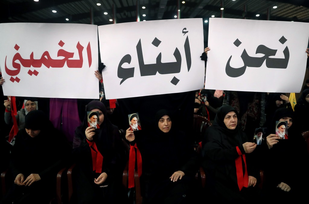 """FILE - In this Feb. 6, 2019 file photo, Hezbollah supporters hold up Arabic placards that read, """"We are the sons of Khomeini,"""" during a rally to comme"""