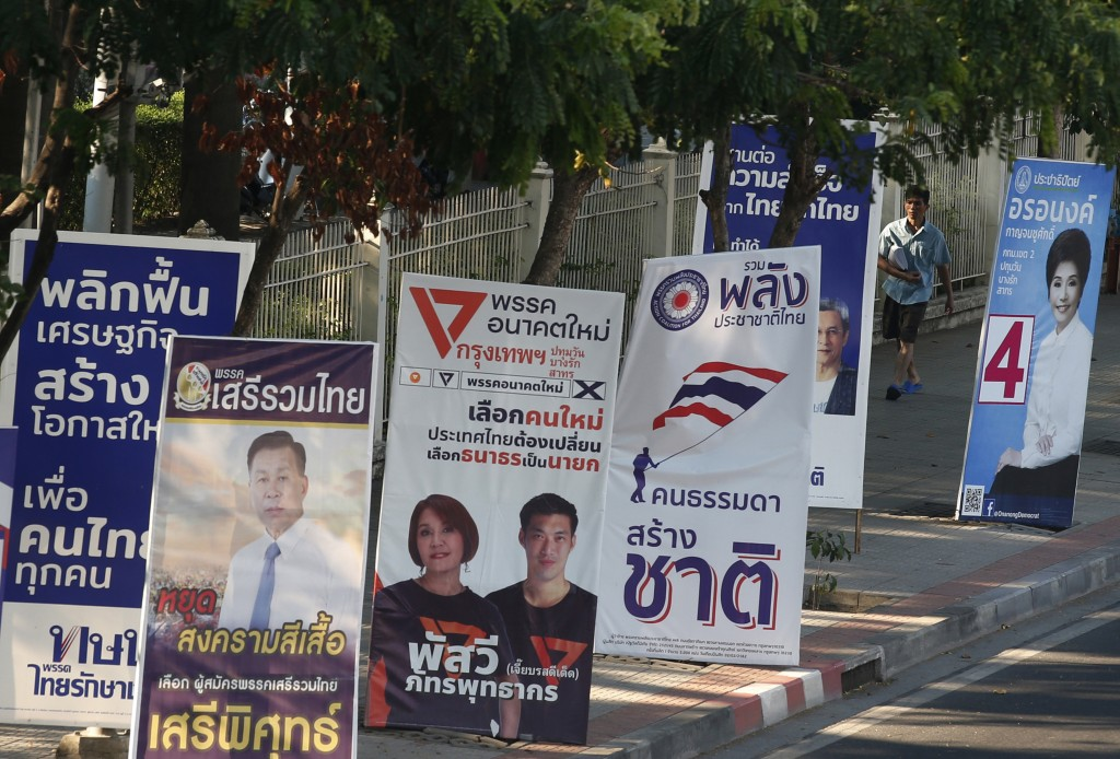 In this March 12, 2019, photo, a pedestrian walks past the election campaign posters in Bangkok, Thailand. Thailand heads to the polls Sunday, March 2