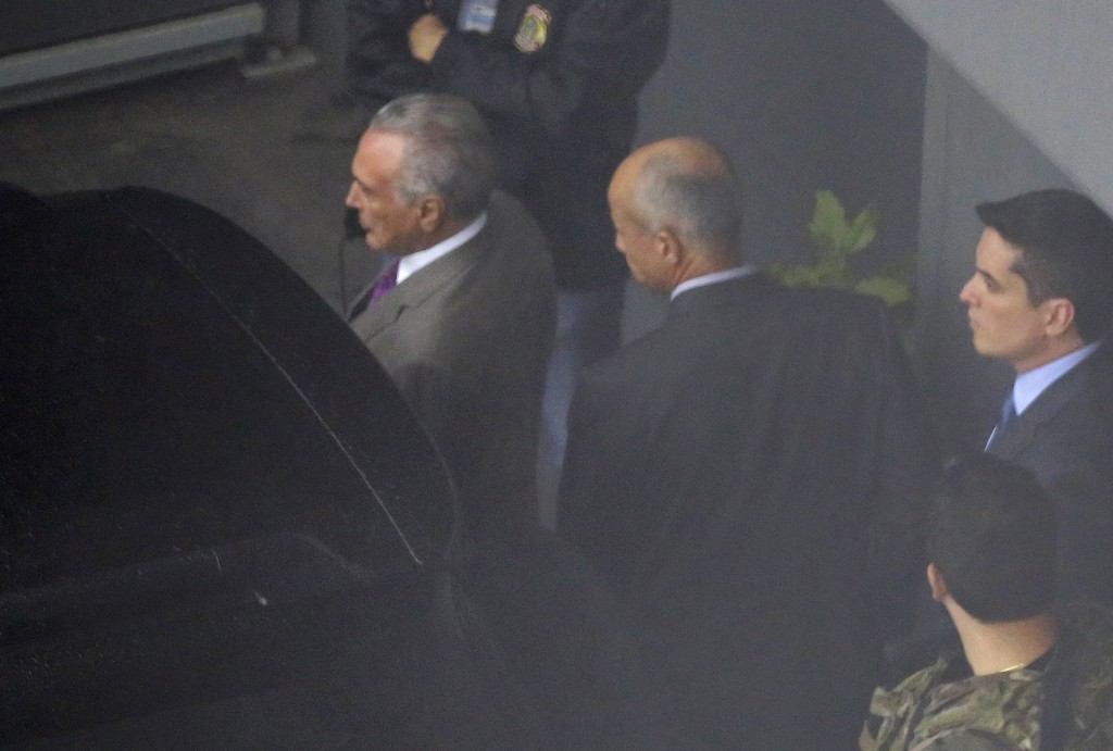 In this photo shot through a fence, former Brazilian President Michel Temer, left, is seen at the international airport in Sao Paulo, Brazil, Thursday