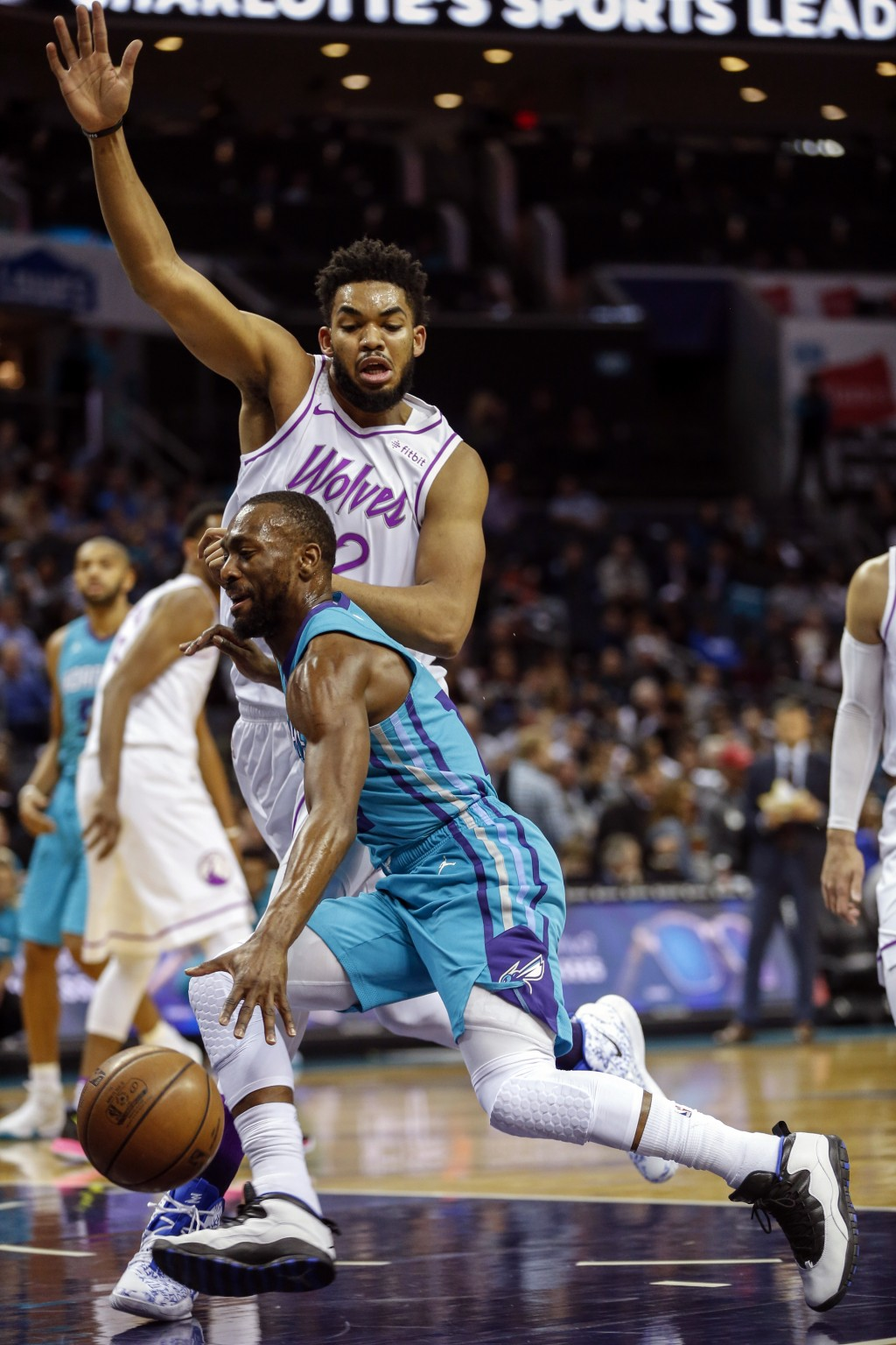Charlotte Hornets guard Kemba Walker, front, drives into Minnesota Timberwolves center Karl-Anthony Towns in the first half of an NBA basketball game