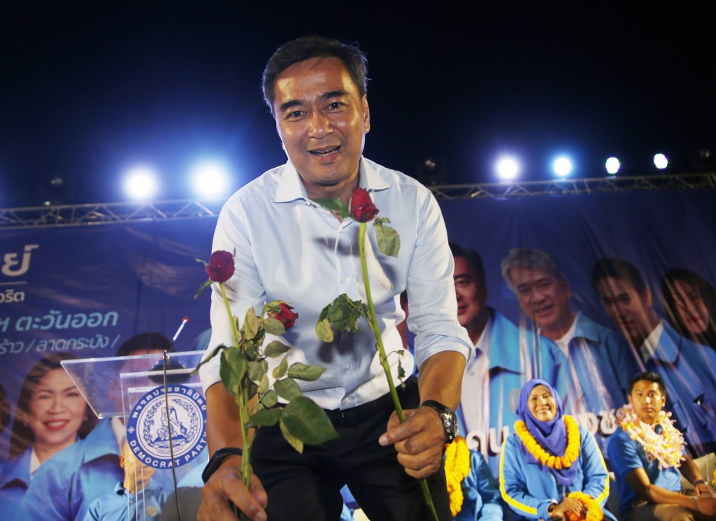 In this March 18, 2019, photo, the leader of Thailand's Democrat Party and prime minister candidate Abhisit Vejjajiva receives flowers from supporters