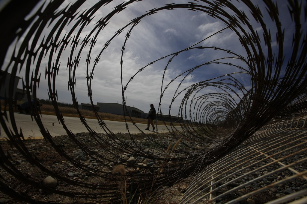 A journalist walks past a fallen section of fencing during a media tour of the now closed Laguna del Toro maximum security facility on the former Isla