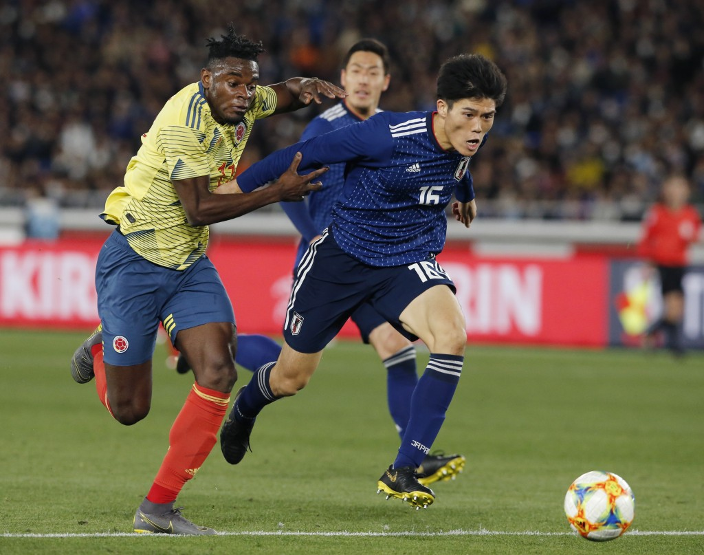 Japan's Takehiro Tomiyasu, right, and Colombia's Duvan Zapata vie for the ball during a friendly soccer match between Japan and Colombia in Yokohama, ...