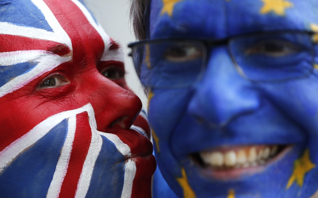 FILE - In this Thursday, March 21, 2019 file photo, activists pose with their faces painted in the EU and Union Flag colors during an anti-Brexit camp