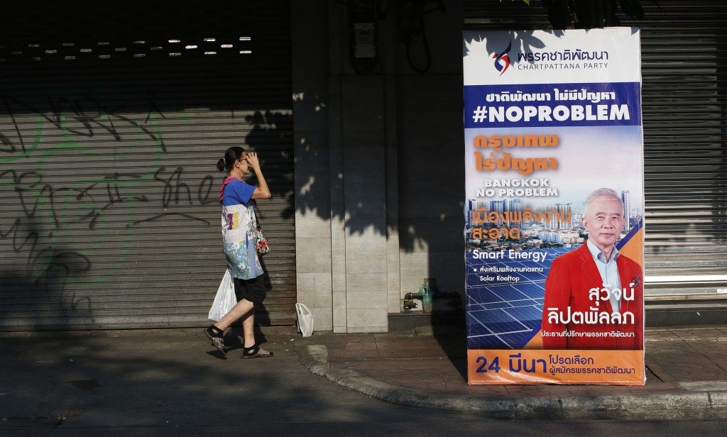 In this  March 15, 2019, photo, a pedestrian walks behind an election campaign poster in Bangkok, Thailand. Thailand heads to the polls Sunday, March
