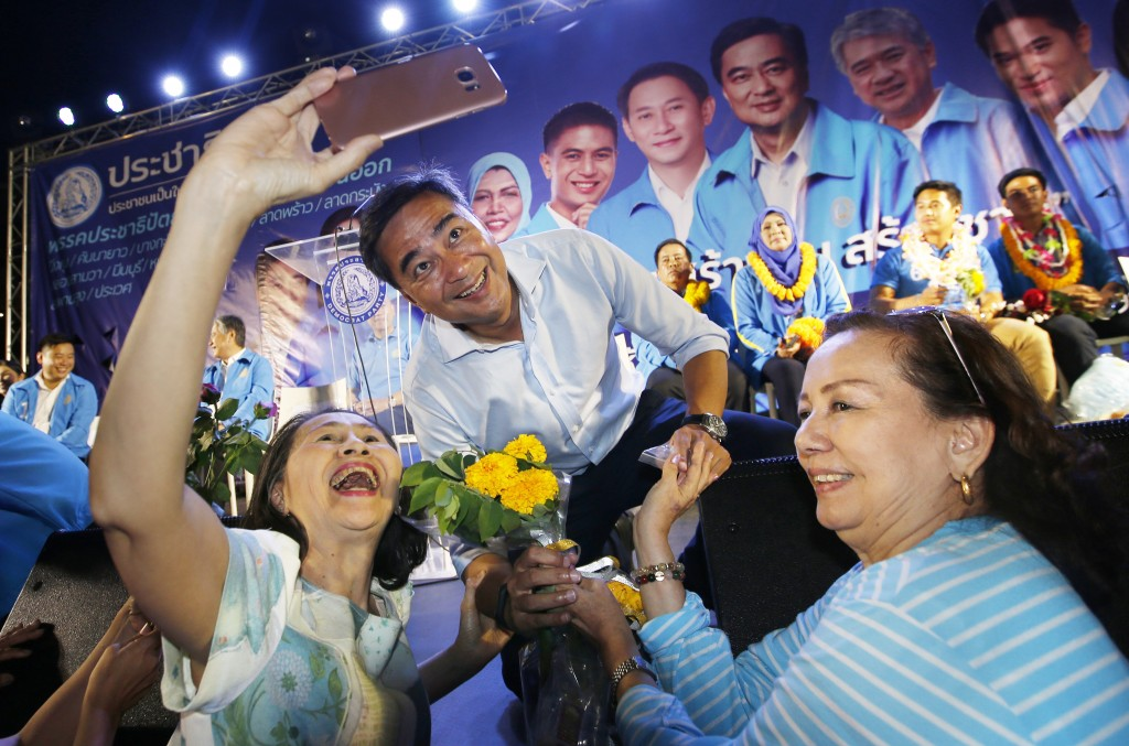 In this March 18, 2019, photo, a supporter takes a selfie with the leader of Thailand's Democrat Party and candidate for prime minister Abhisit Vejjaj