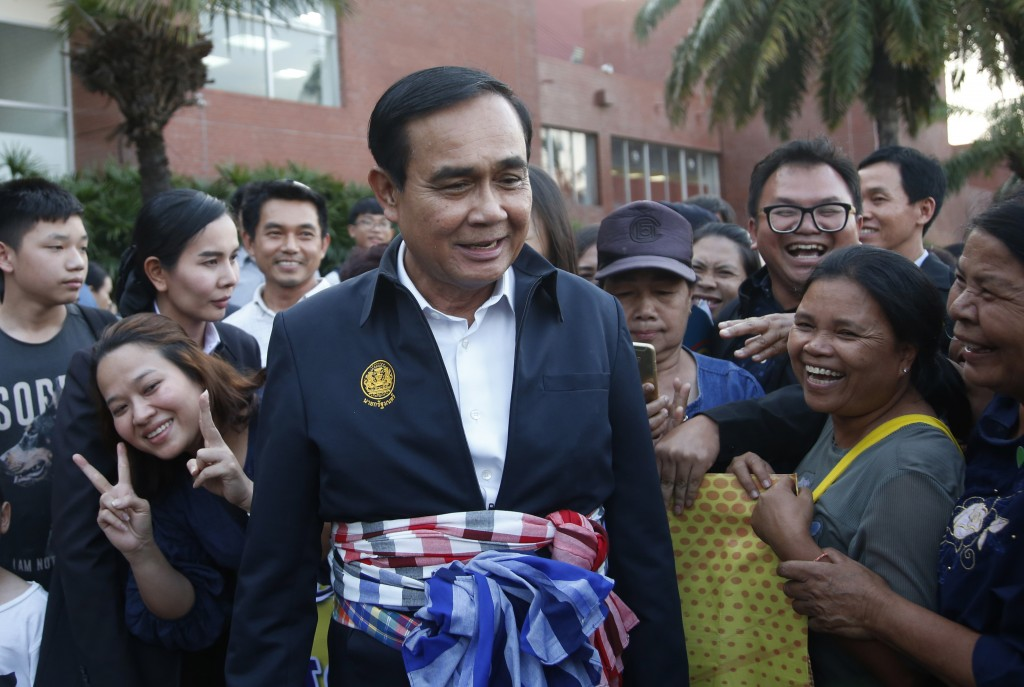 In this March 13, 2019, photo, Thai Prime Minister and candidate for the same position Prayuth Chan-ocha, center, talks with supporters after attendin