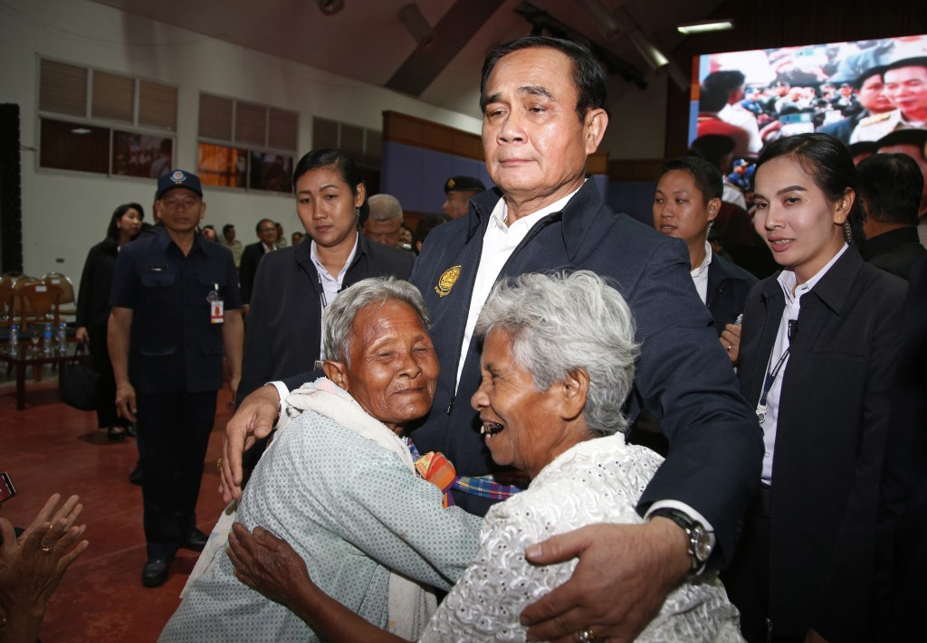 In this March 13, 2019, photo, elderly locals hug Thai Prime Minister Prayuth Chan-ocha, center, and candidate for the same position, as he attends a
