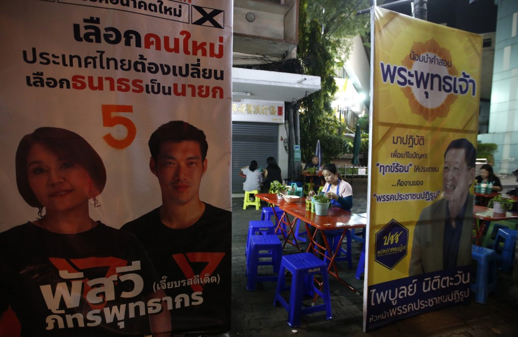 In this Friday, March 15, 2019, photo, election campaign posters surround an outdoor eating area in Bangkok, Thailand. Thailand heads to the polls Sun