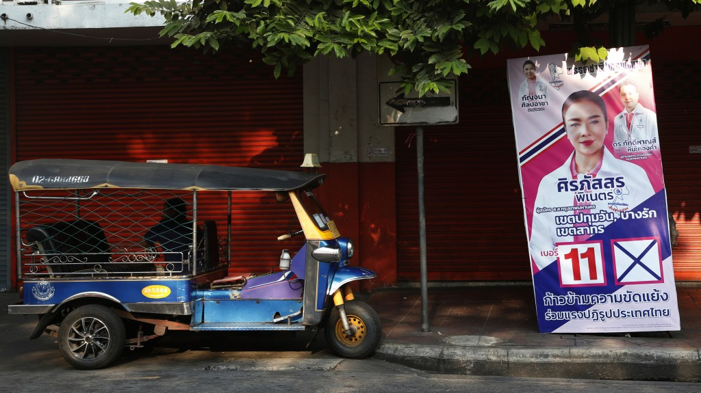 In this March 15, 2019, photo, a tuk-tuk driver waits for customers beside an election campaign poster in Bangkok, Thailand. Thailand heads to the pol